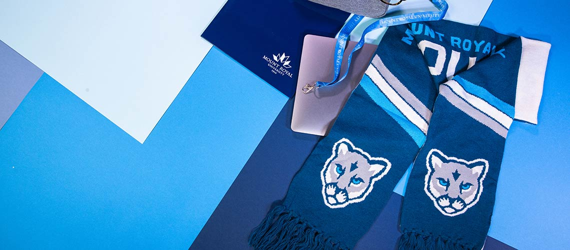 Photo of Mount Royal branded folders, lanyards and a scarf on a multi-coloured, geometric background.